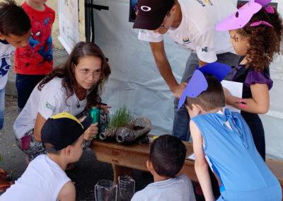 Equipe de Educação Ambiental realiza experimento para mostrar às crianças como a mesma situação, que simula água da chuva, produz diferentes realidades em área com vegetação e sem vegetação