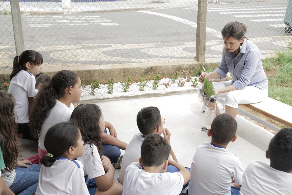 Crianças de Paulínia (SP) observam experimento que simula a infiltração da água em áreas com densa vegetação
